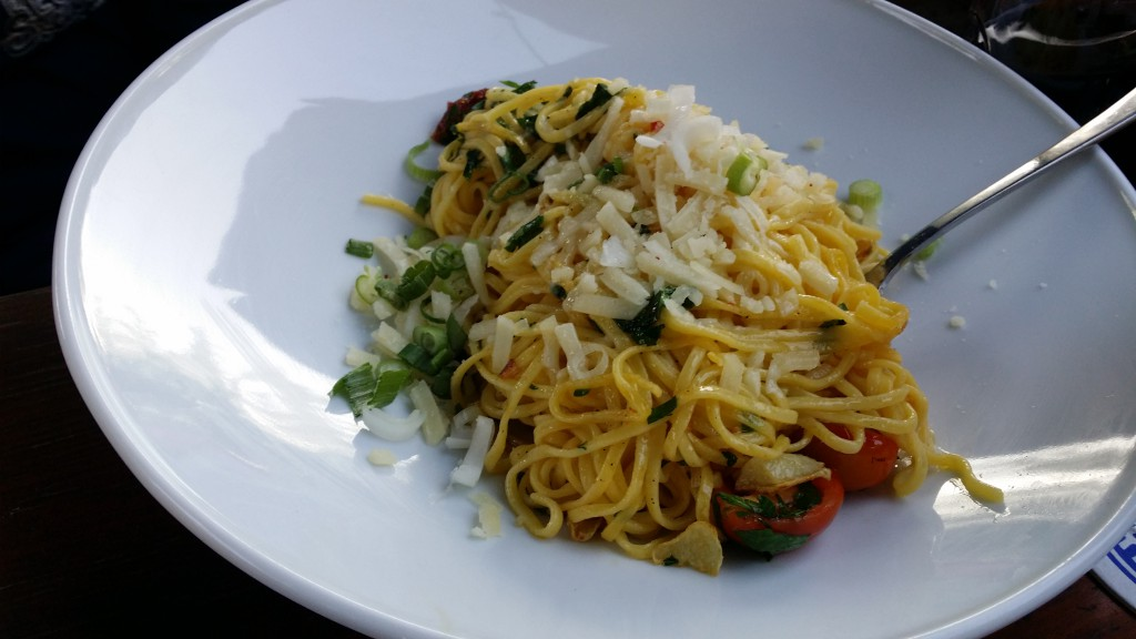 Frische Spaghettini alla Chef in feinem Knoblauch-Chilli-Öl mit frischer Petersilie und Cherrytomaten garniert, dazu Parmesan